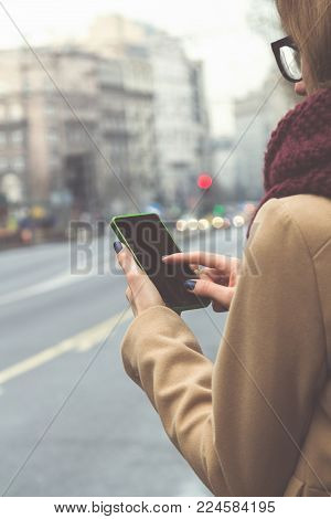 Girl using cellphone while crossing the big street.