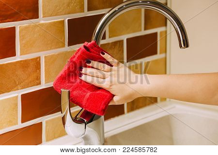 The girl wipes the tap with a red rag, in the kitchen, decorated with a stone.