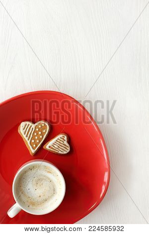 frothy cappuccino with couple of cookies in the shape of heart on red plate top view / breakfast for your favorite person
