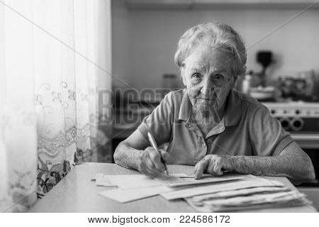 Elderly woman fills out utility bills sitting in the kitchen. Black-and-white photo.