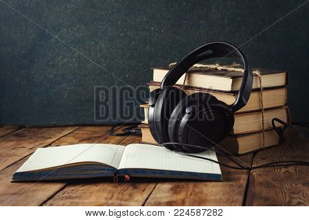 Books stand with a pile, Headphones, outdoor Diary on a wooden background. The Concept of Audio Books and Audio Education.