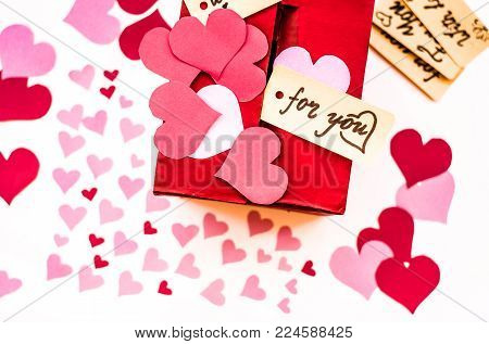 valentine's day holiday. red box for valentines with paper hearts. valentine messages and gift cards