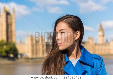 Travel London woman at Westminster, Big Ben, famous holiday destination. Autumn travel lifestyle. Asian girl portrait wearing blue trench coat in urban city.