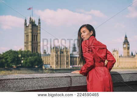 London fashion week Asian model woman at Westminster parliament, iconic british landmark Big Ben city background. Autumn trend lady wearing red trench coat rain outerwear. Europe travel lifestyle.