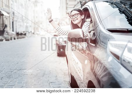 How are you doing. Cheerful millennial woman grinning broadly while seeing her friend and waving to him out of her environmentally friendly electric car.