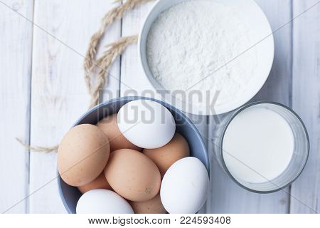 Homamde Pastry, Bakery Concept. A bowl of wheat flour, a bowl of chicken eggs and a glass of fresh organic milk on a white wooden table, top view