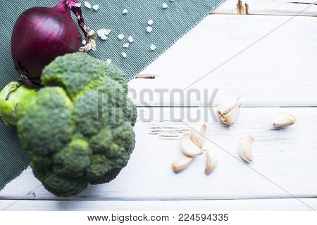 Ready to Cook Vegetarian Meal. A broccoli cabbage head, red onion and garlic cloves, blue linen napkin and white wood as a background, top view
