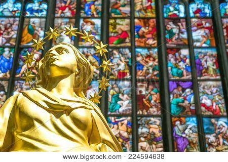 Milan, Italy - October 27, 2016: The interior of the Duomo Cathedral, the colorful stained glass of the apse with the golden statue of the Madonna in the foreground