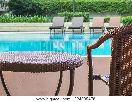 rattan chair on balcony hotel with swimming pool view