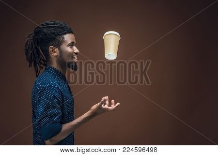 side view of african american man tossing up coffee in paper cup isolated on brown