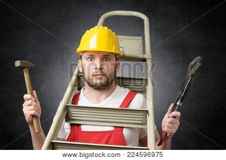 Clumsy worker with ladder, hammer and pipe wrench
