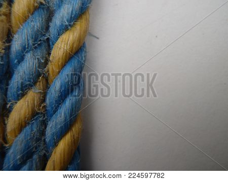 Some blue and yellow rope on a white background