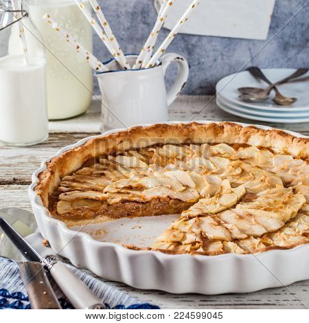 Sliced Round Toffee Apple Tart in a White Ceramic Pan, square