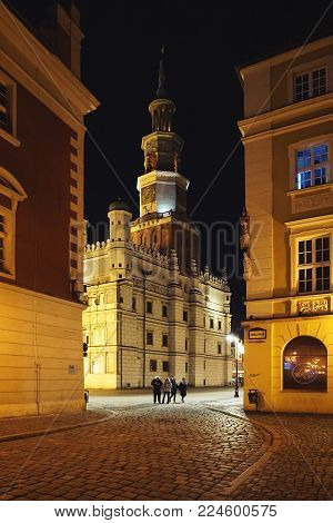Poznan, Poland - January 1, 2018: Townhouse in Poznan with night lighting. Vertical view.