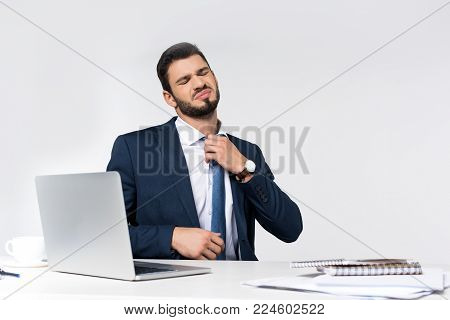 young overworked businessman with closed eyes adjusting necktie while sitting at workplace