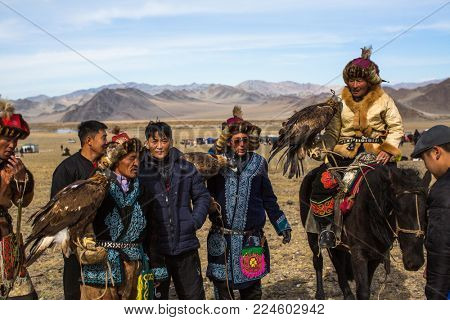 OLGIY, MONGOLIA - SEP 30, 2017: Eagle Hunters at traditional clothing, with a golden eagle on his arm during annual national competition with birds of prey