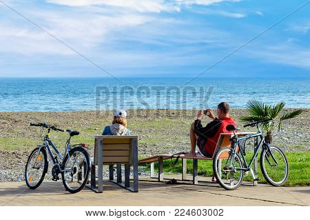 Weekend, Couple Of Adult Caucasian People Sitting On Sun Beds By Sea, Relaxing And Watching Beautifu
