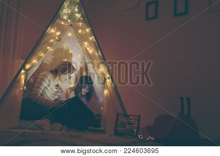 Mother and daughter sitting in a teepee, reading stories with the flashlight. Focus on the mother