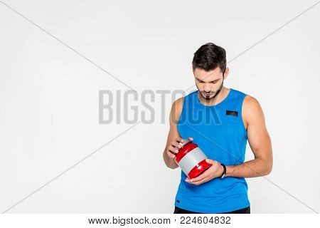 athletic young sportsman holding sport supplement jar isolated on white