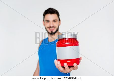 young sportsman holding sport supplement jar isolated on white