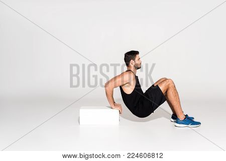 side view of young man doing reverse push ups with block