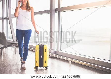 Woman carries your luggage at the airport terminal of Hong Kong, after gonna stady or education fly to Singapore