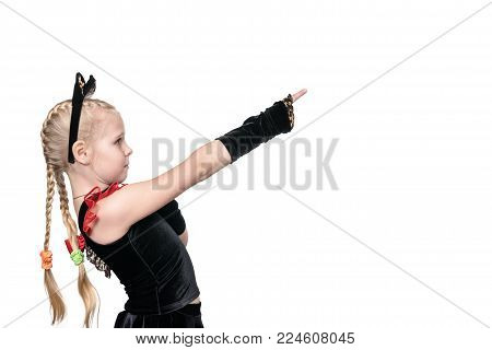 Girl with pigtails in a cat costume points her finger sideways, isolated on a white background