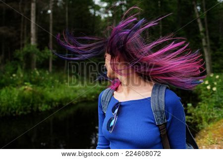 Girls with colored hair. Colored hair coloring, blue pink purple, lilac color. Hair blows the wind, walk along the city street and in the woods on a sunny day.