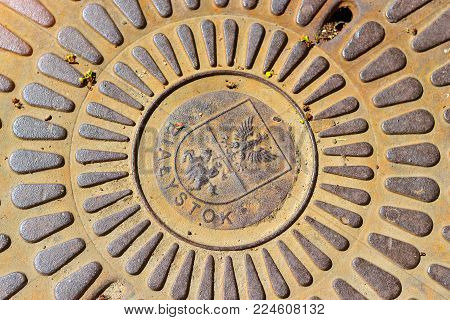 Bialystok, Poland - April 30, 2012: Old cast iron sewerage hatchway cover with the coat of arms of city Bialystok, Poland. Iron manhole on the road of the big city