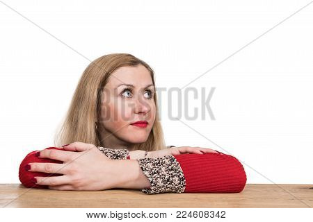 Portrait of a beautiful woman lying at a table with her head raised and looking sideways, isolated on a white background