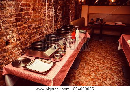 Several cooktops with frying pans in kitchen for cooking workshop