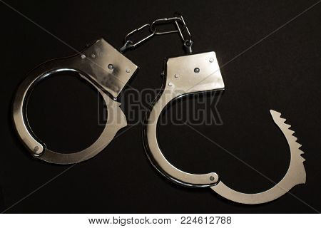 Handcuffs on black background (old white metal)