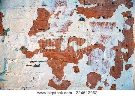 Close up obsolete weathered brixk wall with cracked peeling ehite paint