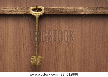 An old key that hangs on a wooden wall. The key hanging on the hanger