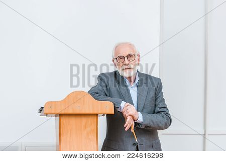 senior lecturer leaning on wooden tribune in classroom