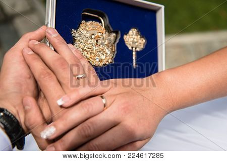 Close-up image of hands of bride and groom and wedding accessory of beautiful metal lock and key in box
