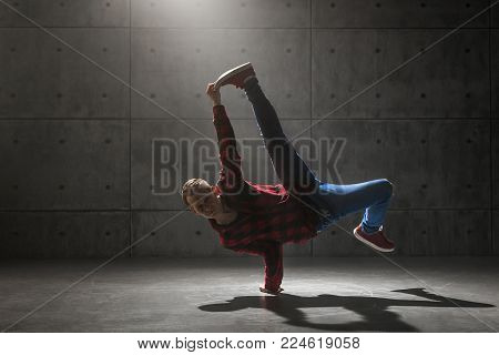 Young stylish male breakdancer posing in studio