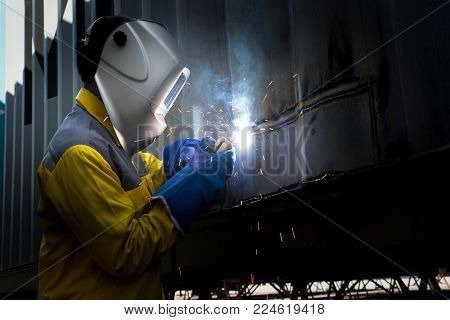 Industry worker with welding steel to repair container structures manufacture workshop. Container maintenance industry.