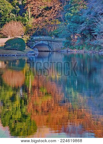 Japanese garden autumn pond reflections with small stone arch bridge. Beautiful colorful rippled Monet water color like reflections naturally lighting up this Japanese feature pond with stone bridge in Tokyo, Japan.