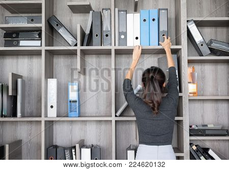 Secretary or Purchasing Manager  in a modern Office shelves room. Setup studio shooting.