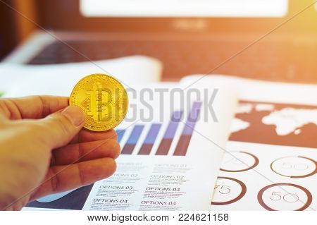 Crypto currency gold bitcoin.Man holding coin symbol of crypto currency - Electronic virtual money for web banking or electronic commerce payment, selective focus.