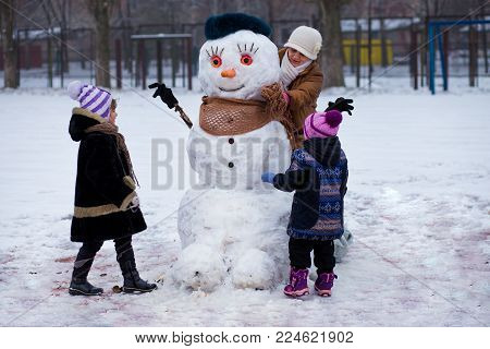 Happy grandmother and little granddaughters sculpt a big real snowman, Happy family play in a winter park