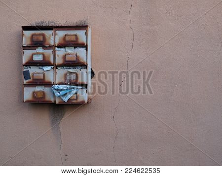 Abandoned rusty mailboxes with deteriorating stuffed mail adorn the side of an abandoned house. Time passing by, but some things will stay the same. Homelessness, poverty, underprivileged or apocalyptic?