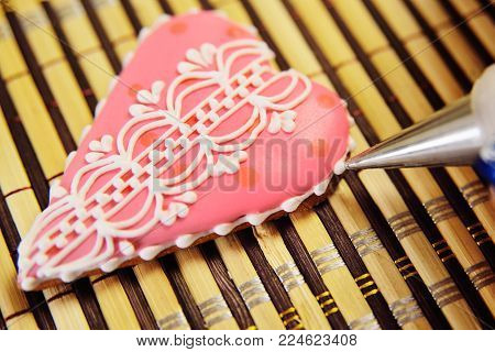woman confectioner decorates and decorates the glaze with gingerbread cookies in the shape of heart. Valentine's Day, February 14, symbol, valentine, gift.