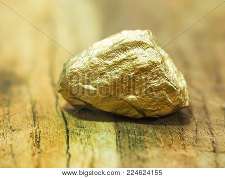 macro Gold ore in the boulder , precious stone on wooden background