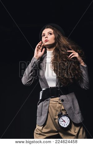 low angle view of fashionable pensive young woman with clock looking away isolated on black