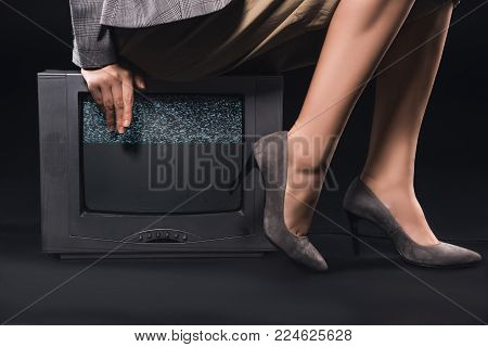 cropped shot of stylish woman sitting on tv with noises on the screen on black