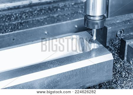 The CNC machine cutting the automobile part in the light blue scene.Automobile parts manufacturing process.
