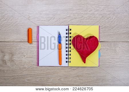 Open notebook with ballpoint pen and red heart of wool on a burlap background, top view