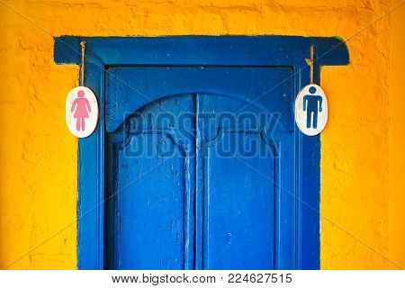 The combination of yellow and blue in the architecture of Indonesian buildings. The plate on the door is a male and female toilet.